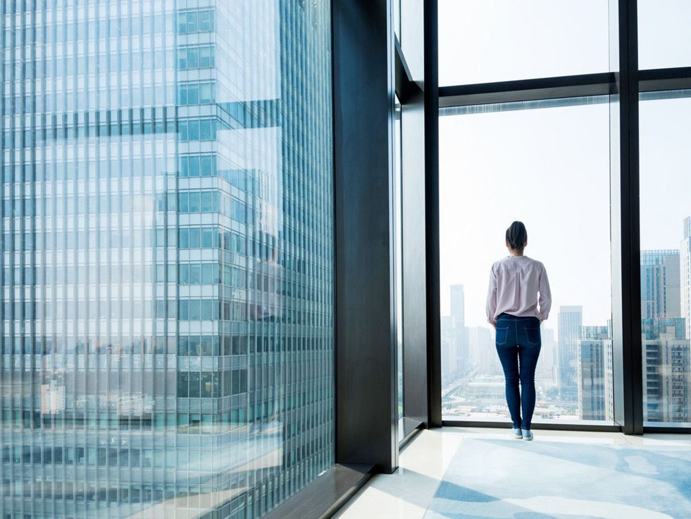 Woman standing and looking at cityscape from office