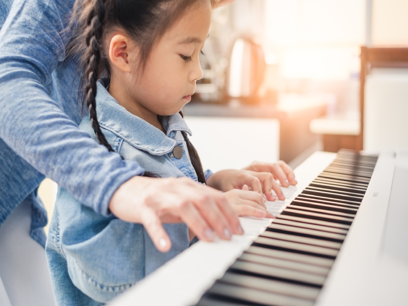 Young girl learns how to play piano in home that uses a YORK Steam Humidifier for improved air quality.