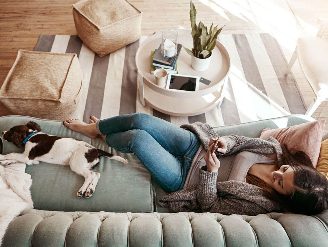 A woman relaxing on the sofa with her dog and using a mobile phone