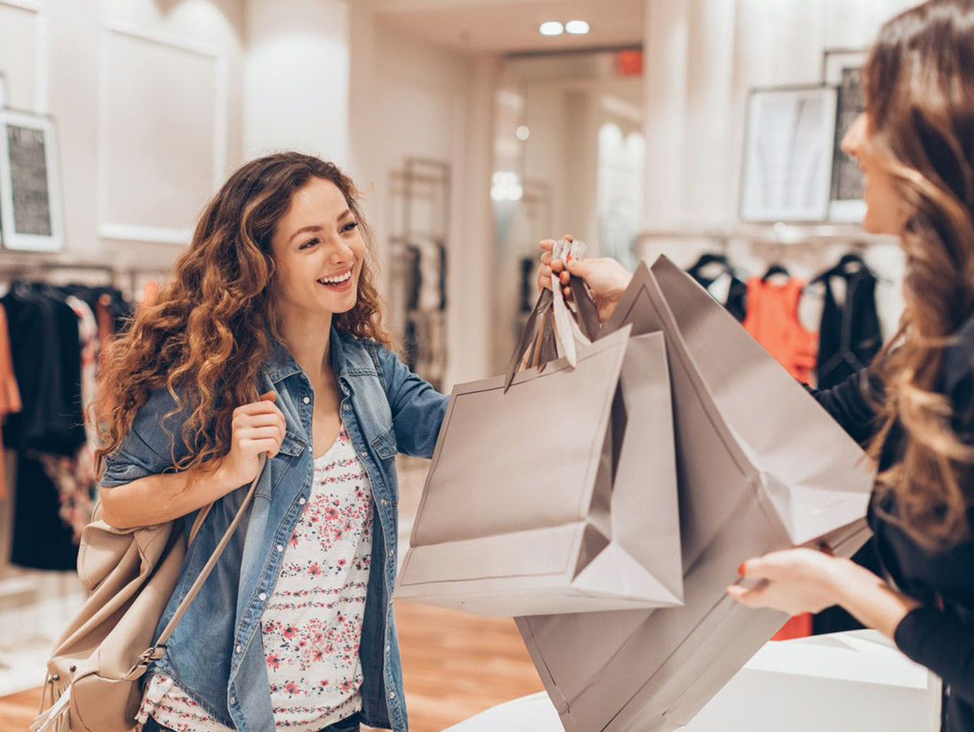 A saleswoman giving shopping bags to a woman in a fashion store