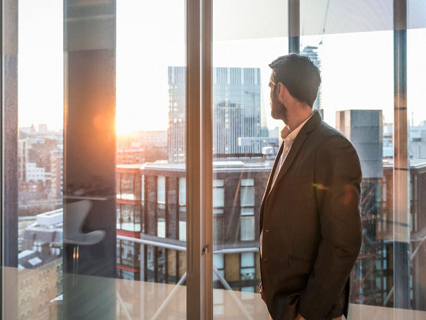 Office worker looking at view through window of modern office over city
