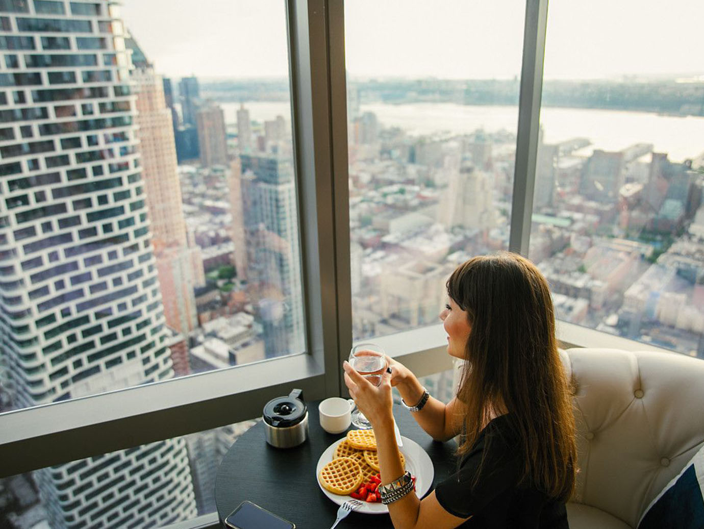 Woman having breakfast and coffee with the city view in the background