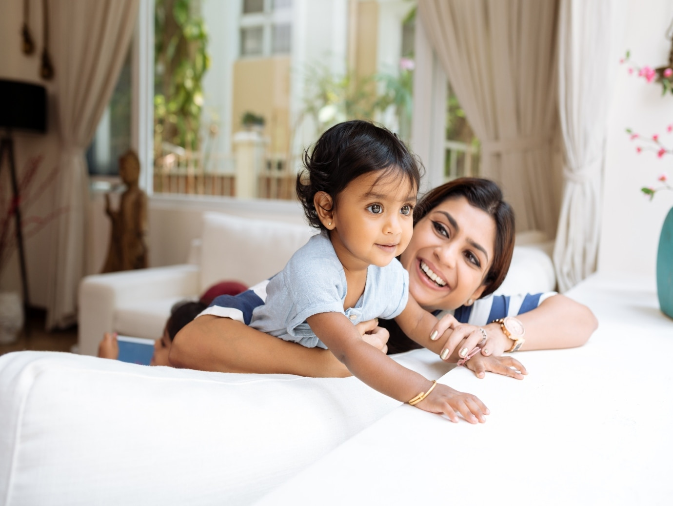 Happy child and mother play on the couch in home that uses a YORK Air Conditioner for reliable operation and comfort.