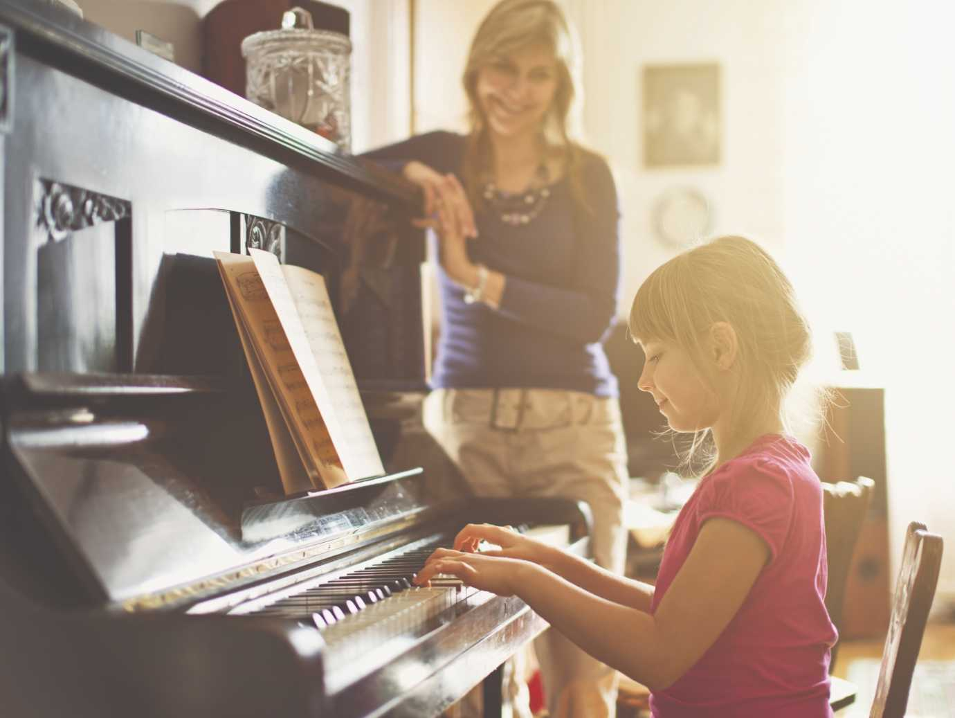 Child plays piano while mother watches in a home that uses a YORK Gas Furnace.
