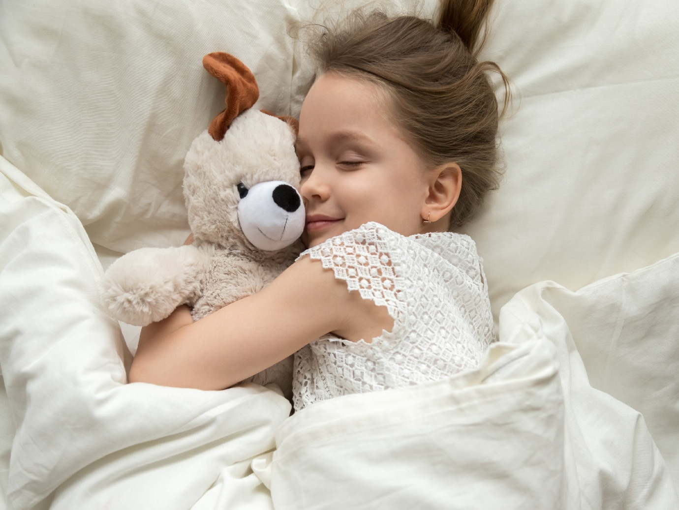 YORK Indoor Air Quality system used for a healthy indoor environment in home of a young girl laying in bed hugging her bear.