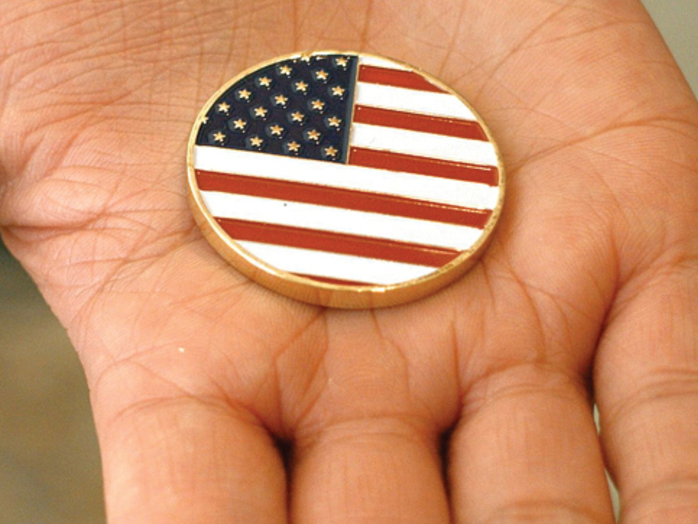 A hand holding United States flag badge